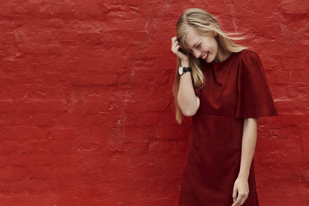 Red dress woman laughing against red wall
